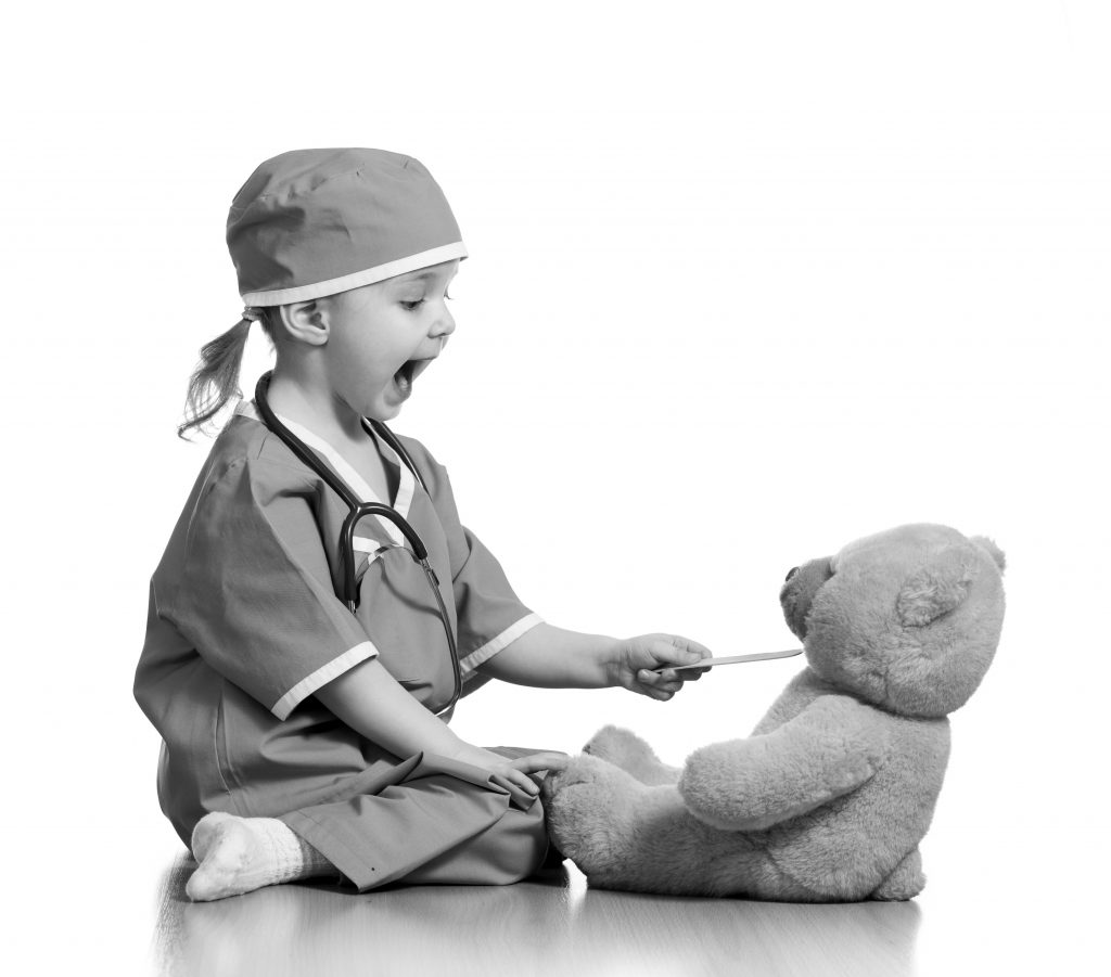 Adorable child dressed as doctor playing with toy over white background